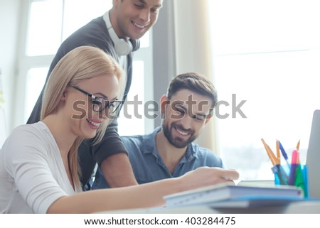 Talented young colleagues are working in cooperation - stock photo