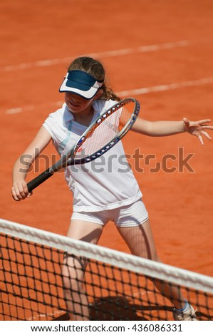 Talented young tennis player on the net - stock photo