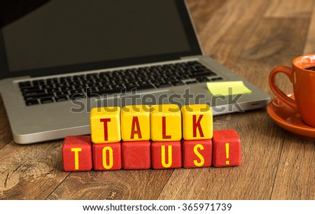 Talk to Us! written on a wooden cube in a office desk - stock photo