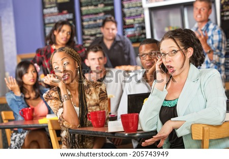 Talkative female on cell phone annoying students in cafe - stock photo