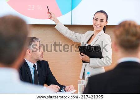 Talking about achievements. Confident young woman in formalwear pointing projection screen and smiling while making presentation in conference hall with people on foreground - stock photo