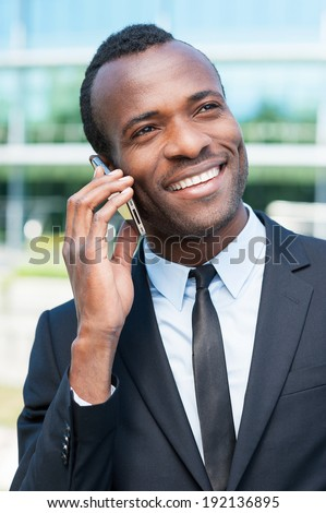 Talking about business. Cheerful young African man in formal wear talking on the mobile phone and smiling while standing outdoors - stock photo