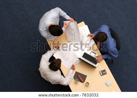 talking about plans - three working business people over plans.Aerial shot taken from directly above the table - stock photo