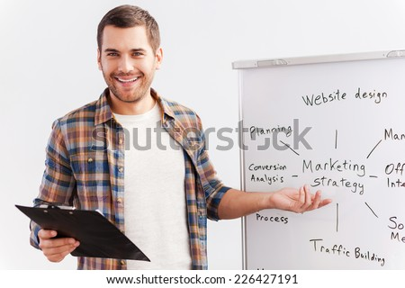 Talking about strategy. Confident young man in smart casual wear standing near whiteboard and pointing it with smile - stock photo