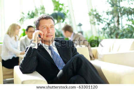 Talking business over the phone and smiling - stock photo