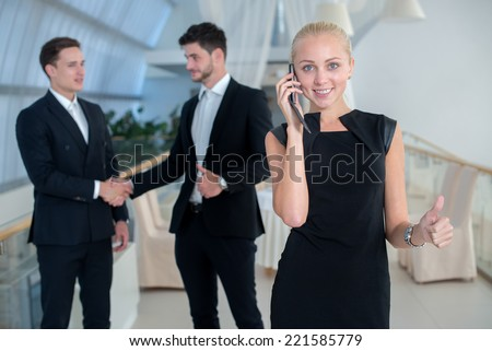 Talking by mobile phone. Successful business woman speaks by mobile phone. Two businessmen are standing on the background and shaking their hands