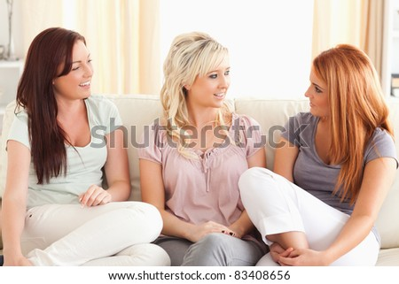 Talking friends sitting on a sofa in a living room - stock photo
