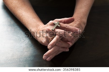 talking hands concept - female hands holding a religious cross praying for confession on dark wooden table,studio shot