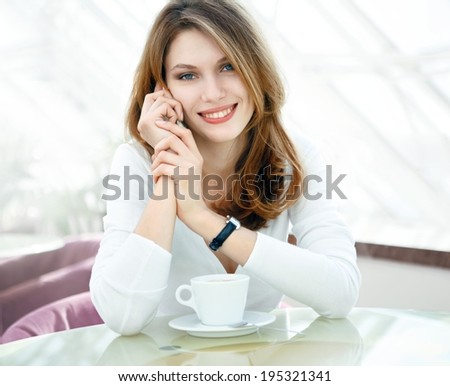 Talking on cell phone / photo of beautiful woman sitting in a coffee house