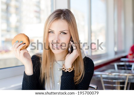 talking on mobile cell phone and having lunch happy smiling looking at camera beautiful young business woman cute blond girl having fun relaxing in restaurant or coffee shop close up portrait image