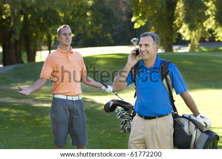 Talking on the cell phone while playing golf is annoying - stock photo