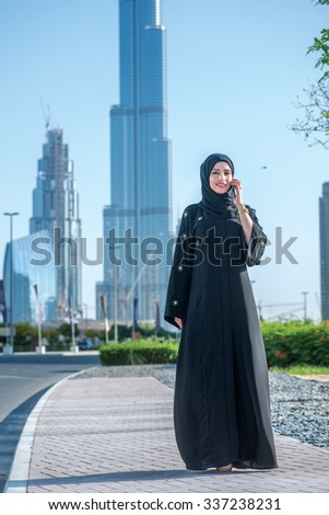Talking on the phone with a client in Dubai. Arab Business vumen hijab talking on a cell phone on the street on a background of skyscrapers of Dubai. The woman is dressed in a black abaya - stock photo