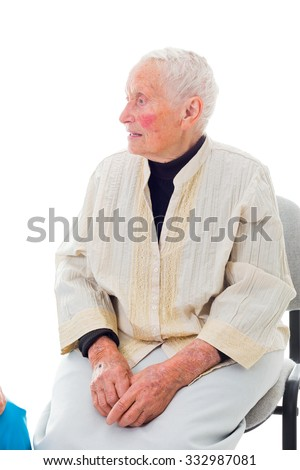 Talking senior lady sitting on chair and looking to her right.