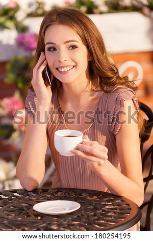 Talking with friend. Attractive young woman talking on the mobile phone and smiling while sitting at the outdoor cafe - stock photo