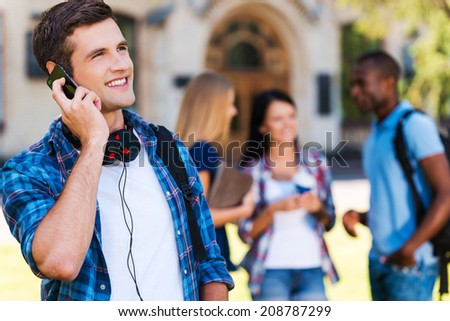 Talking with friends. Handsome young man talking on the mobile phone and smiling while standing against university building with his friends chatting in the background - stock photo