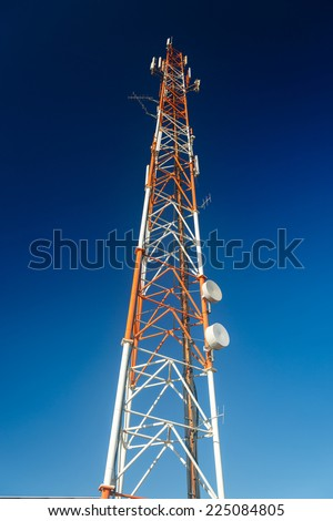 Tall antenna mast isolated on blue sky background - stock photo