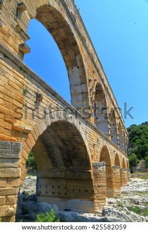 Tall arches of the Roman aqueduct of Pont du Gard, Nimes, France - stock photo
