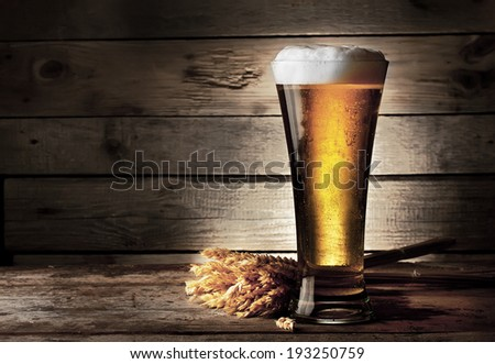 Tall beer glass with beer and ears on wooden background - stock photo