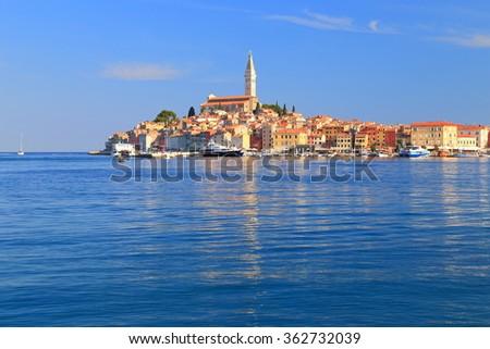 Tall belfry of Venetian church above historical buildings of Rovinj, Croatia - stock photo