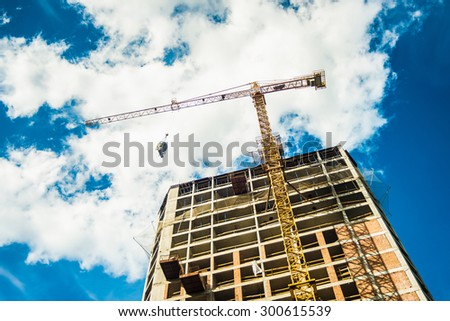 Tall building construction and crane under a blue sky with clouds - stock photo