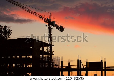 Tall building under construction over beautiful sunset sky - stock photo