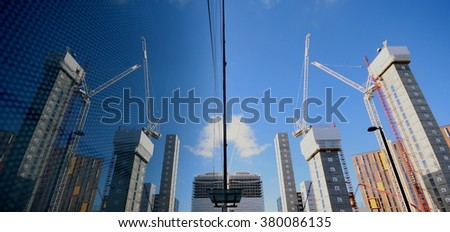 Tall buildings on a construction site reflected on glass in Wembley, London - stock photo