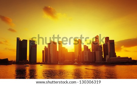 Tall buildings reflecting in a water during sunset - stock photo