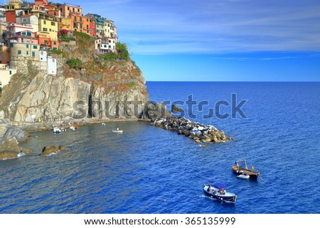 Tall cliffs near the sea and Manarola village at sunset, Cinque Terre, Italy - stock photo
