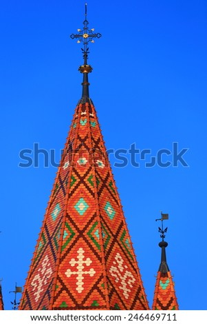 Tall cross above the decorated roof of St Matthias church in Budapest, Hungary - stock photo