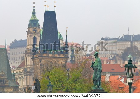 Tall domes and Gothic tower behind religious statues on Charles bridge, Prague, Czech Republic - stock photo