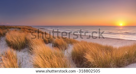 Tall dunes with dune grass and a wide beach below. Photographed at sunset on the island of Texel in The Netherlands. - stock photo