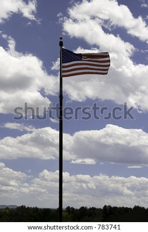 Tall flag pole with American flag at the top blowing in the wind on a beautiful blue sky and fluffy white clouds day.  This view shows the entire flag pole with a slight tree top view.