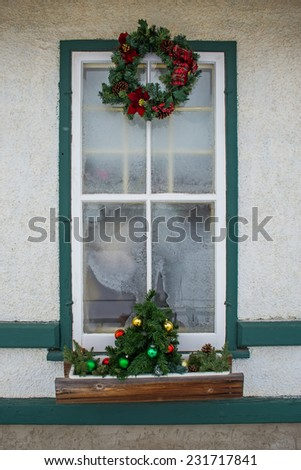 Tall frosted window decorated with Christmas wreath and small tree