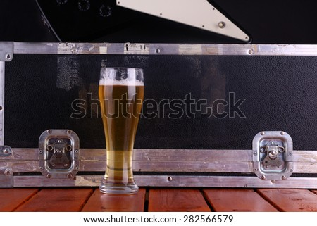 Tall glass full of light beer standing on a wooden table with a music equipment case and guitar in the background - stock photo