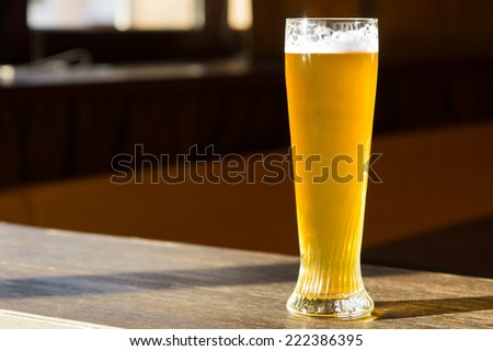 Tall Glass of Beer in Sunray on Table - stock photo