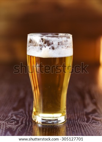 tall glass of beer on wooden background - stock photo