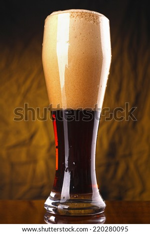 Tall glass of dark beer over a yellow lit background