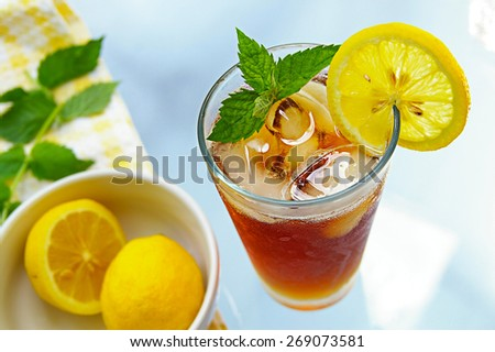 tall glass of iced tea with lemon and fresh mint - stock photo