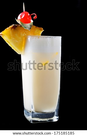 Tall glass of Pina Colada Cocktail made with rum, cream of coconut, and pineapple juice served garnished with fresh pineapple and maraschino cherry - stock photo