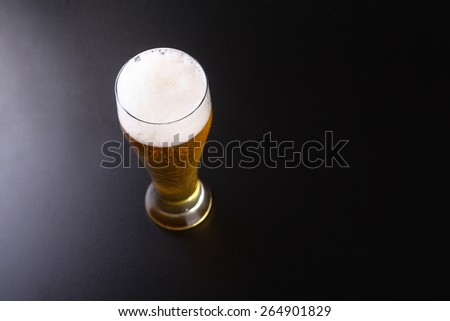 Tall glass of sparkling lager beer over a dark background - stock photo