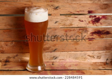 Tall glass of wheat beer standing in an old dirty wooden crate