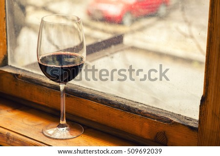Tall glass of wine on a wood windowsill