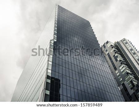 Tall glass office tower on an overcast day - the BHP Billiton Centre in Melbourne, Australia. - stock photo