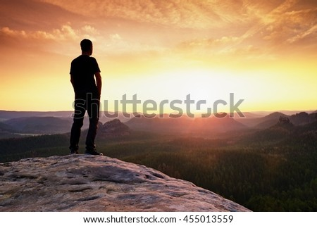 Tall hiker has his hands on hips. Thinking man silhouette in nature within daybreak. The vignetting effect.