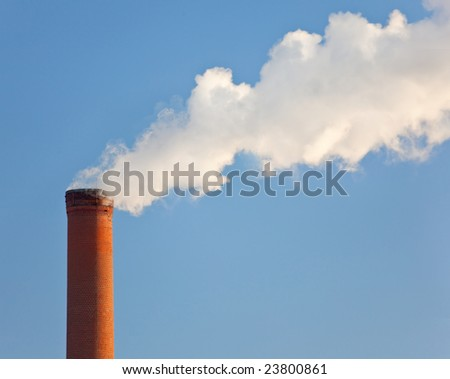 Tall industrial brick chimney venting gasses into the atmosphere