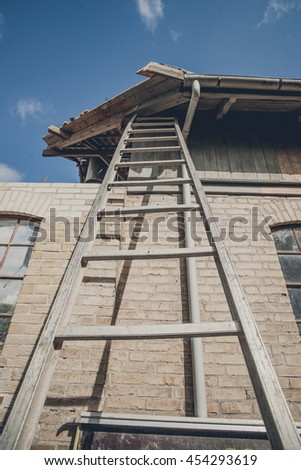 Tall ladder at an old building with damaged roof - stock photo