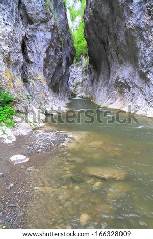Tall limestone walls create small gorge with water flowing - stock photo