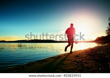 Tall man in running cloths  at amazing sunset in sport and healthy lifestyle concept and jogging cross country training workout