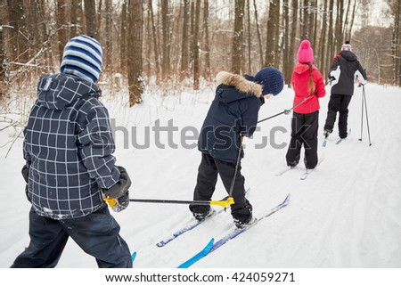Tall man pulls three children chained with ski-poles one behind other on skis in winter park. - stock photo