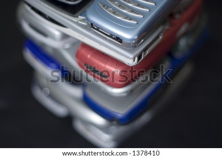 Tall pile of mobile cellular handsets. A mini telecom Tower ready for collection by charity. - stock photo